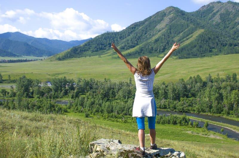 La muchacha con las manos aumentadas en las montañas Altai Rusia la visión superior imágenes de archivo libres de regalías