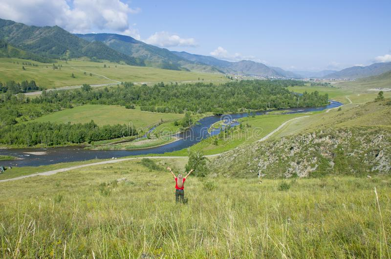 La muchacha con las manos aumentadas en las montañas Altai Rusia la visión superior imagen de archivo libre de regalías