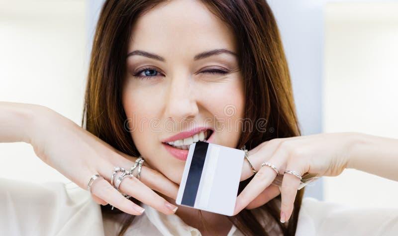 La muchacha con las porciones de anillos en las manos guarda la tarjeta de crédito imagen de archivo libre de regalías
