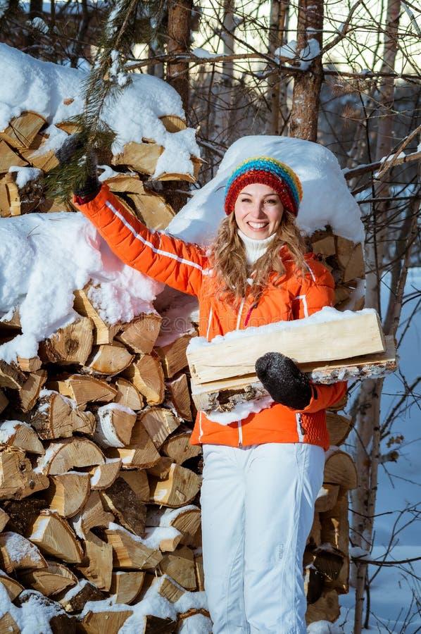 La muchacha con leña en el invierno imagen de archivo