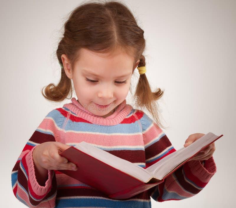 La muchacha con los arqueamientos lee el libro imagen de archivo