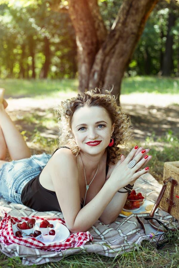 La muchacha con los labios rojos está comiendo la fresa en comida campestre imagen de archivo