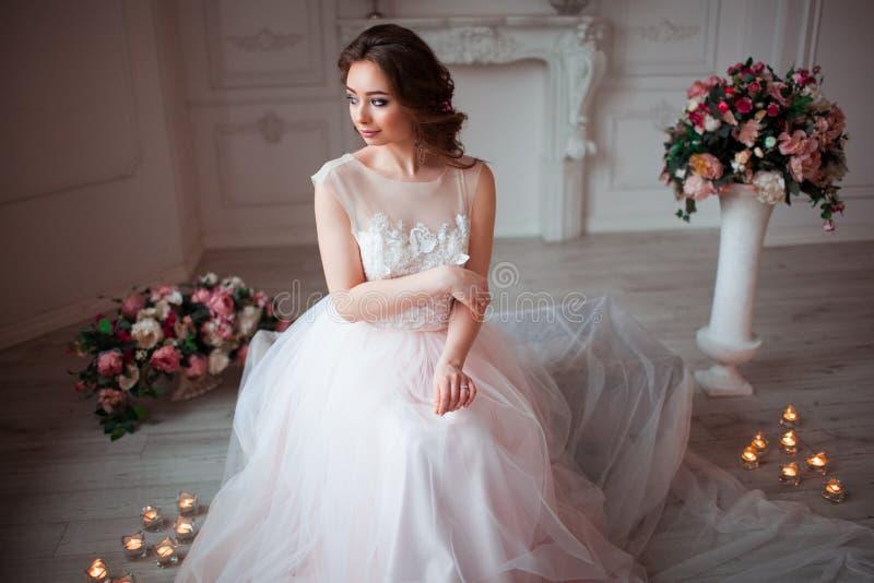 La muchacha con maquillaje en un vestido de boda rosado se está sentando en un cuarto hermoso rodeado por las flores y las velas imagenes de archivo