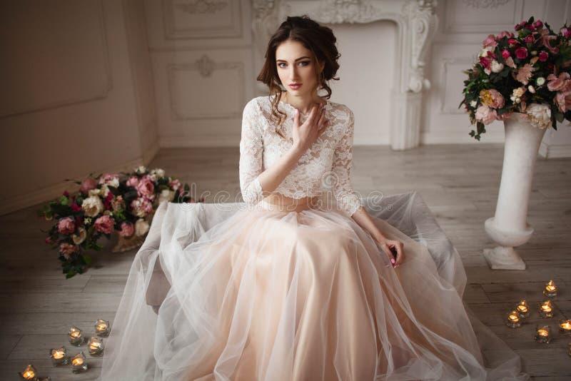 La muchacha con maquillaje en un vestido de boda se sienta en un cuarto hermoso foto de archivo