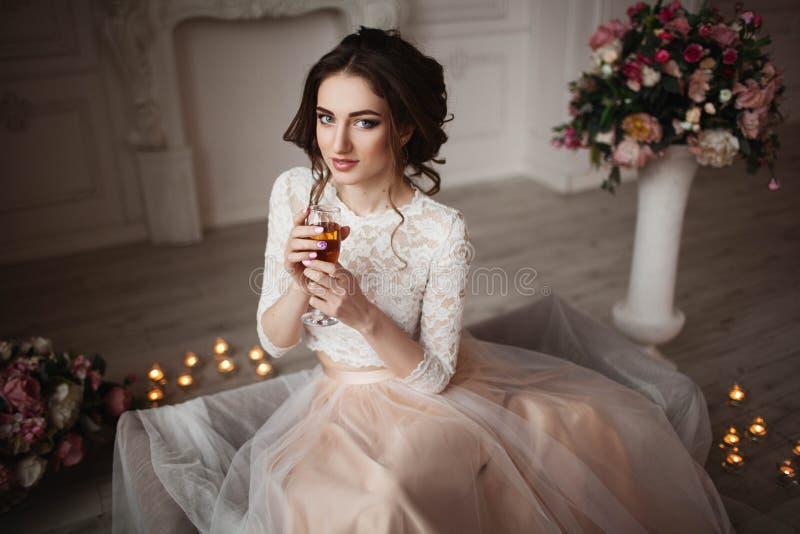 La muchacha con maquillaje en un vestido de boda se sienta en un cuarto hermoso imágenes de archivo libres de regalías