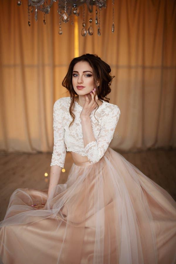 La muchacha con maquillaje en un vestido de boda se sienta en un cuarto hermoso foto de archivo libre de regalías