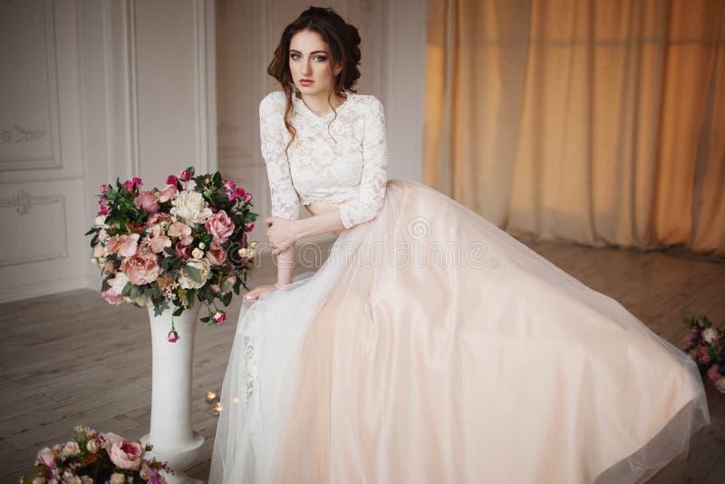 La muchacha con maquillaje en un vestido de boda se sienta en un cuarto hermoso fotos de archivo libres de regalías