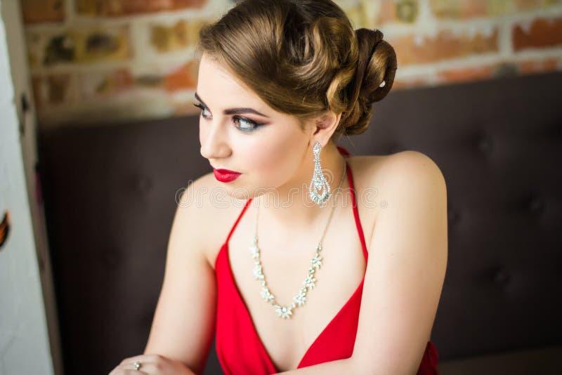 La muchacha con maquillaje y labios rojos mira cuidadosamente a un lado imagenes de archivo