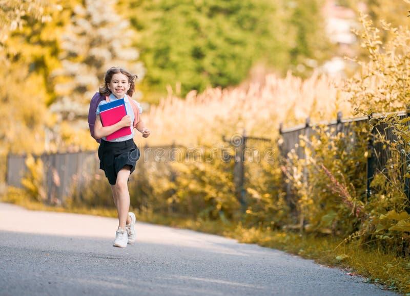La muchacha con la mochila va a enseñar imagen de archivo libre de regalías