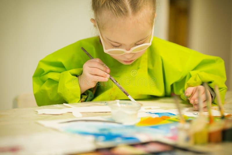 La muchacha con Síndrome de Down dibuja las pinturas fotos de archivo