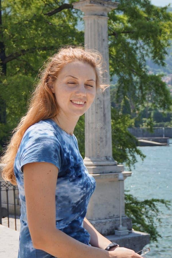 La muchacha con sus ojos cerrados se sienta en el parapeto de la costa de Bellagio en el lago Como imagenes de archivo