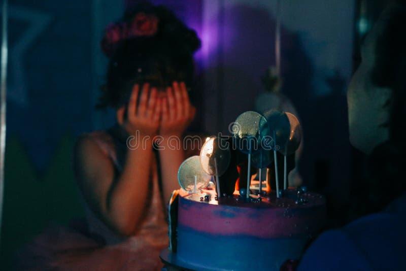 La muchacha con la torta de cumpleaños se cerró los ojos con sus manos que hacían un deseo en el sitio oscuro, quemado las velas imágenes de archivo libres de regalías