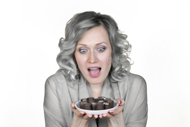 La muchacha con un apetito mira el caramelo en sus manos foto de archivo libre de regalías