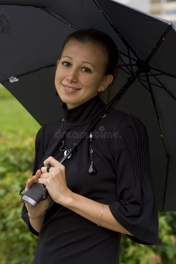 La muchacha con un paraguas fotografía de archivo libre de regalías