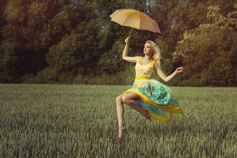 La muchacha con un paraguas eleva y mantiene flotando fotos de archivo libres de regalías