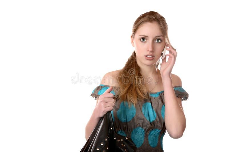 La muchacha con un teléfono portátil foto de archivo