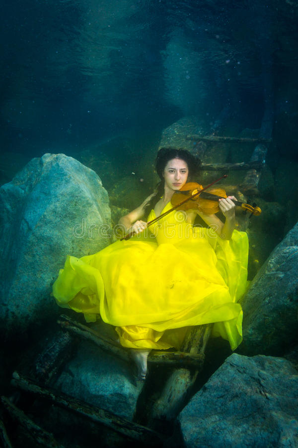 La muchacha con un violín debajo del agua foto de archivo