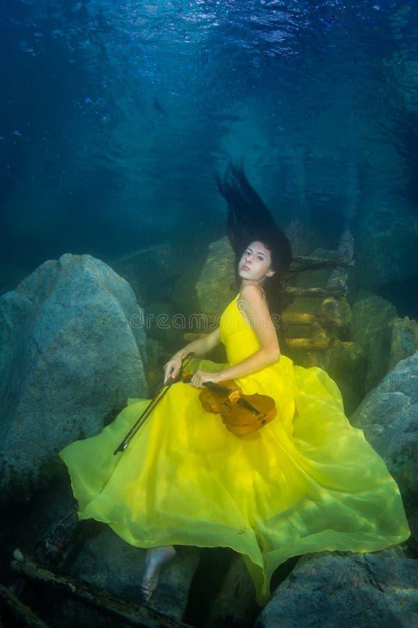 La muchacha con un violín debajo del agua fotos de archivo libres de regalías