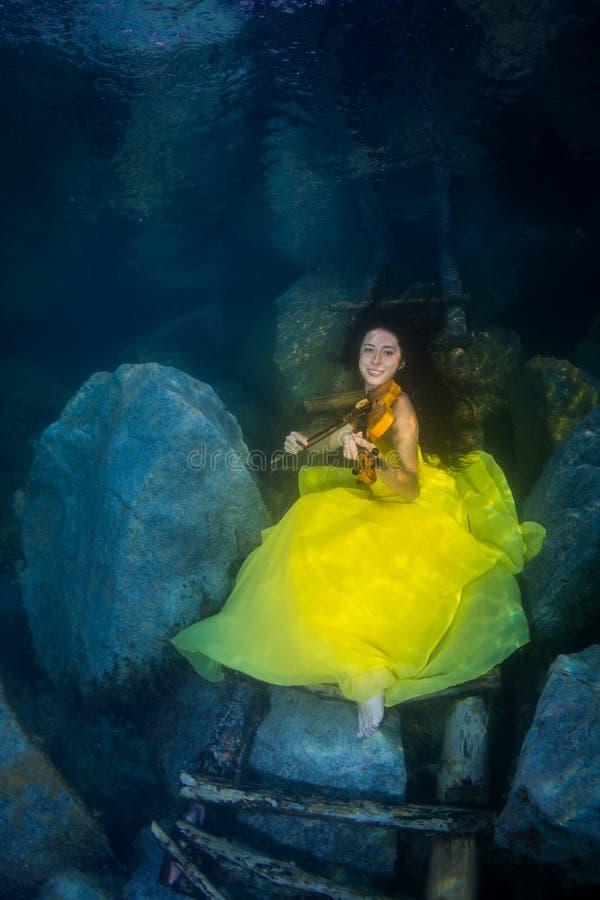 La muchacha con un violín debajo del agua fotos de archivo