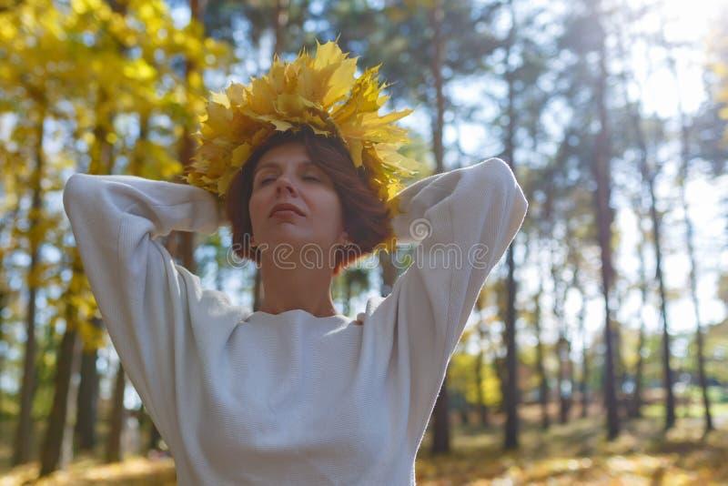 La muchacha con una guirnalda de hojas de arce amarillas en su cabeza se está colocando con los ojos cerrados y el goce del día c foto de archivo