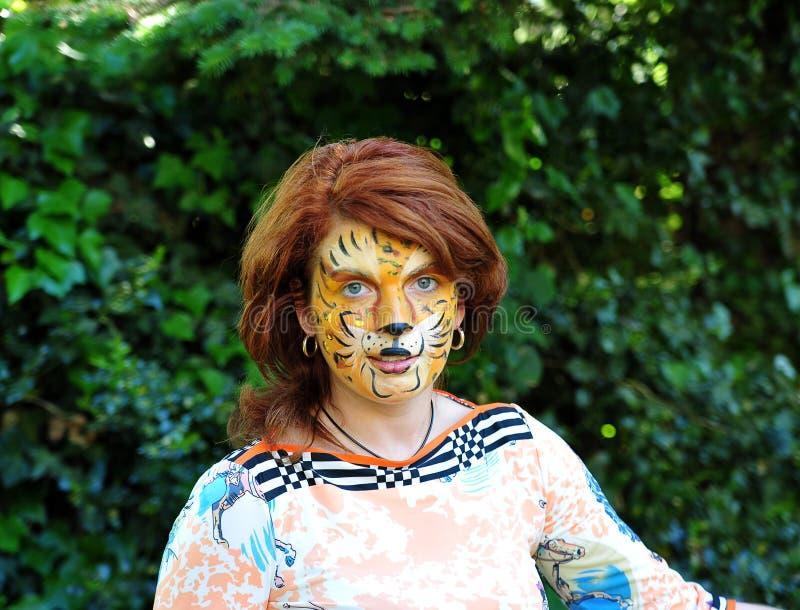 La muchacha con una imagen de un tigre en la cara fotografía de archivo