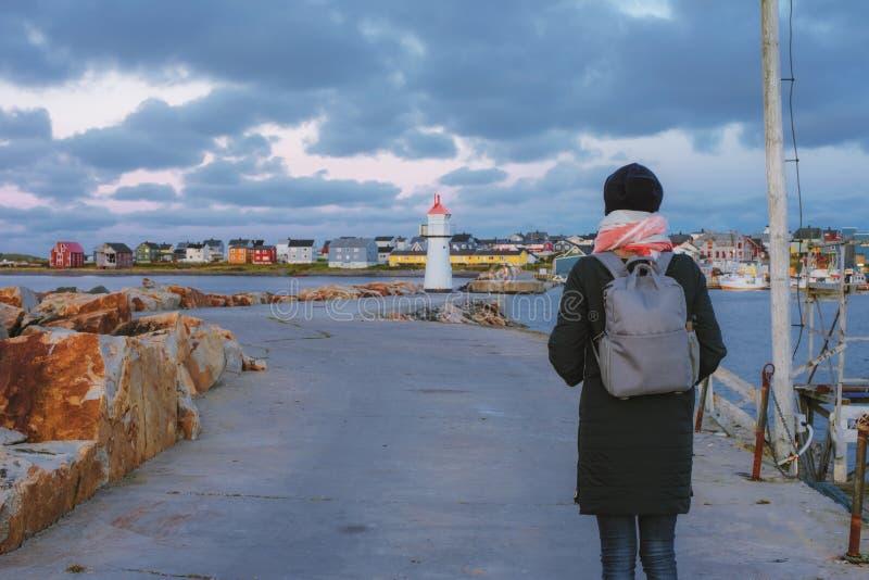 La muchacha con una mochila que va al faro en el amarre en Vardo, Noruega foto de archivo