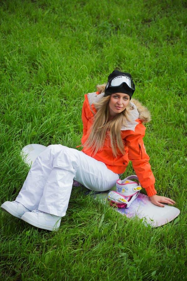 La muchacha con una snowboard se está sentando en la hierba imagenes de archivo