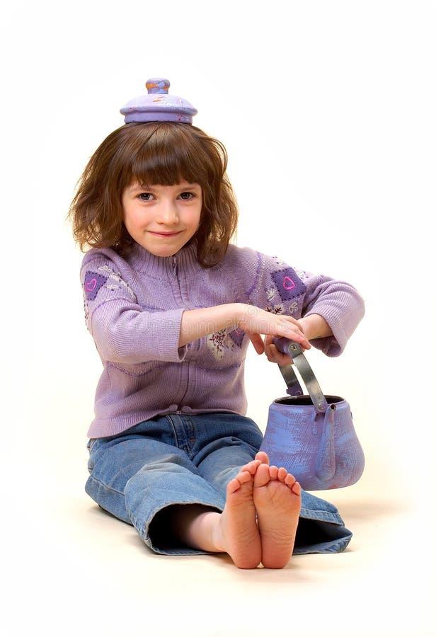 La muchacha con una tetera foto de archivo