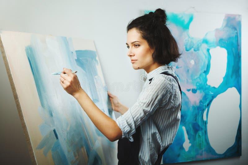 La muchacha concentrada se centró en proceso de arte-fabricación creativo en terapia del arte imagen de archivo