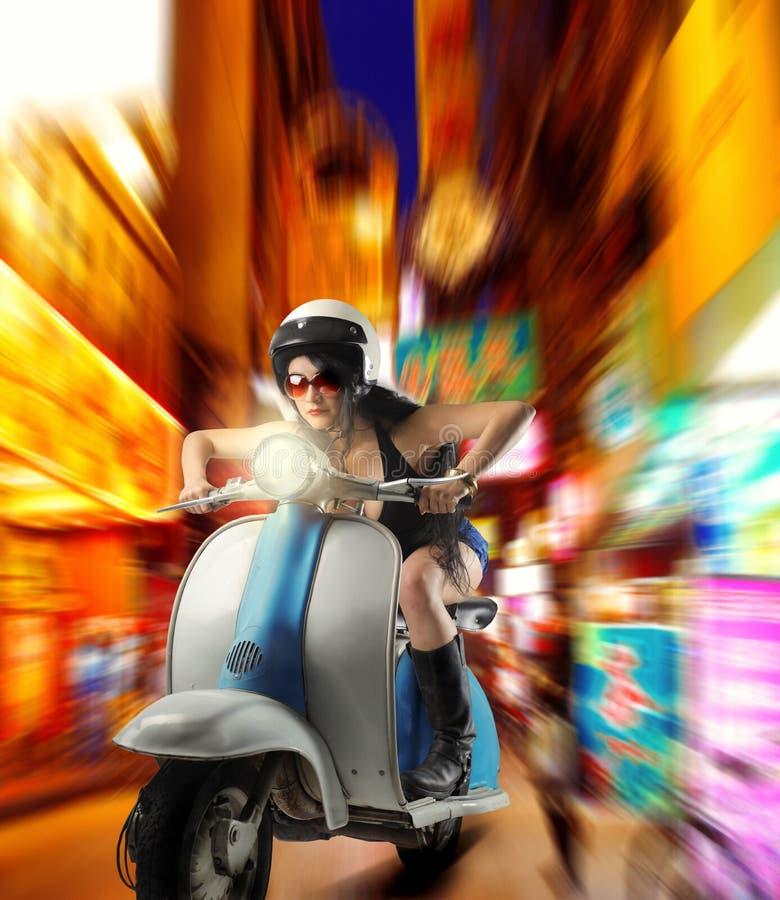 La muchacha conduce el ciclomotor foto de archivo
