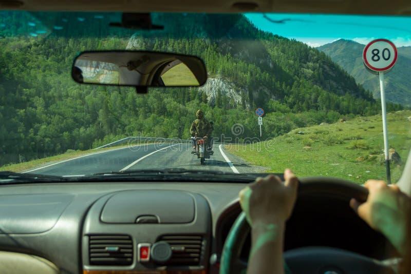 La muchacha conduce a lo largo de la carretera de asfalto en el al de las montañas de Altai imágenes de archivo libres de regalías