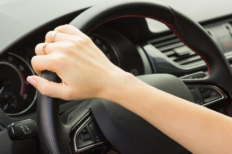 La muchacha conduce un coche, sostiene el volante con una mano imagenes de archivo