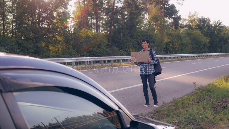 La muchacha consigue la ciudad que hace autostop fotografía de archivo libre de regalías