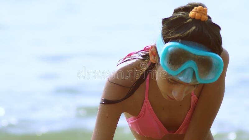 La muchacha construye un castillo de la arena en una playa tropical Primer foto de archivo