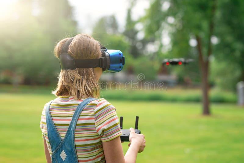 La muchacha controla un quadrocopter en el parque con la ayuda de un casco de VR El concepto de realidad virtual realidad adicion