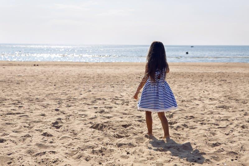 La muchacha corre detrás a lo largo de la playa fotos de archivo libres de regalías