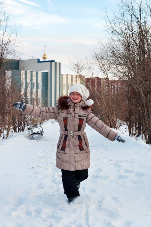 La muchacha corre en un callejón nevoso. fotos de archivo