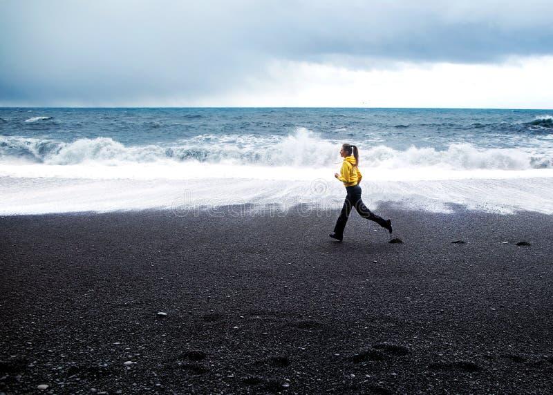La muchacha corre a lo largo de la playa cerca del Océano Atlántico en Islandia imagen de archivo