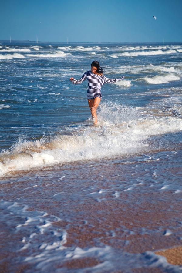 La muchacha corre a lo largo de la playa en las ondas, estado de ánimo feliz imagen de archivo