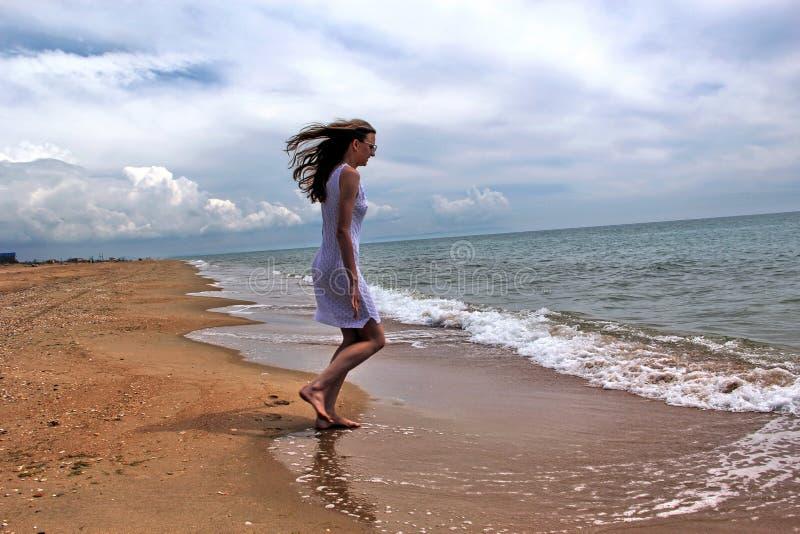 La muchacha corre a lo largo de la playa imagen de archivo libre de regalías