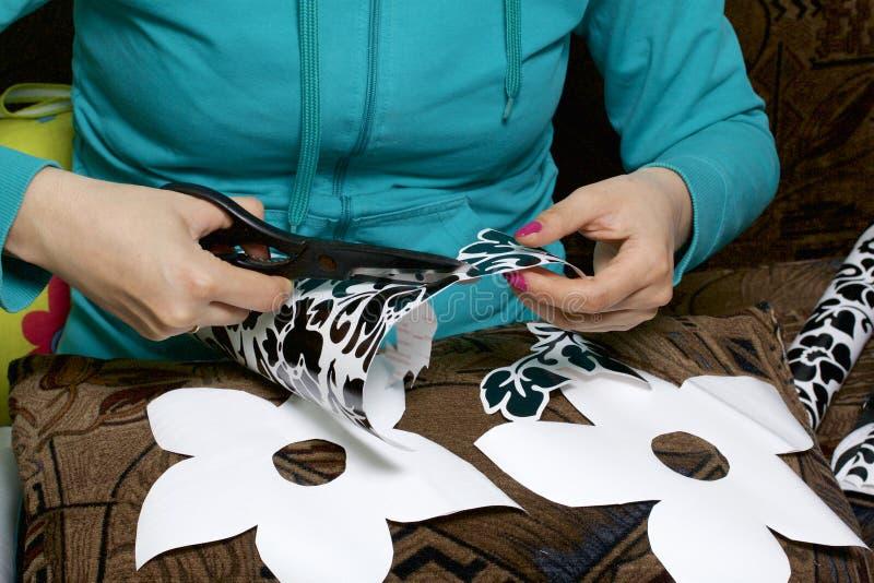 La muchacha cortó elementos del papel auto-adhesivo, para enmascarar los defectos de la puerta blanca imagen de archivo