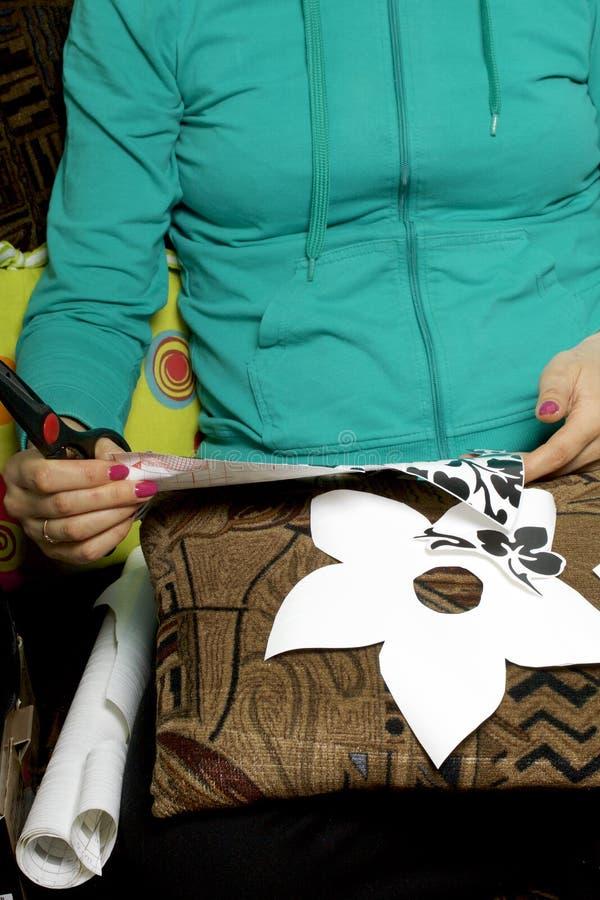 La muchacha cortó elementos del papel auto-adhesivo, para enmascarar los defectos de la puerta blanca fotos de archivo