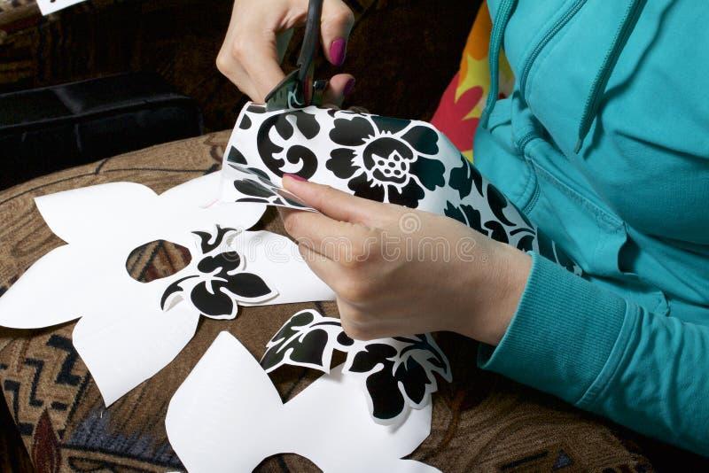 La muchacha cortó elementos del papel auto-adhesivo, para enmascarar los defectos de la puerta blanca fotografía de archivo