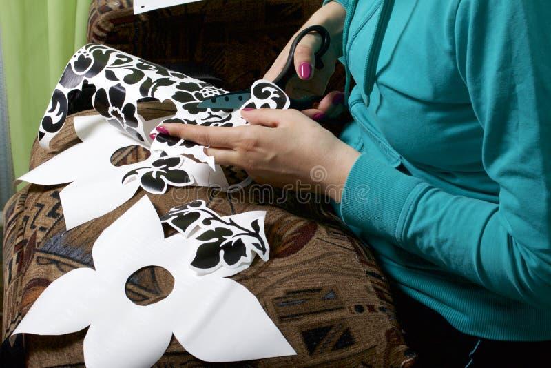 La muchacha cortó elementos del papel auto-adhesivo, para enmascarar los defectos de la puerta blanca fotos de archivo libres de regalías