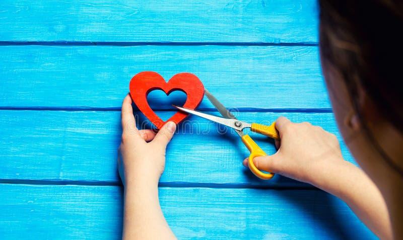 la muchacha corta el corazón con las tijeras, el concepto de romper relaciones, peleas y divorcio Traición del othere Parte poste fotos de archivo