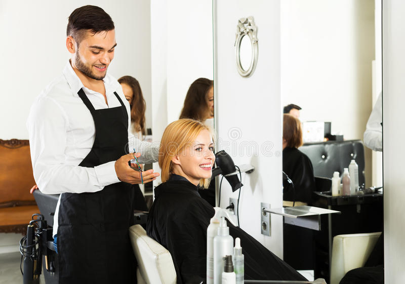 La muchacha corta el pelo en el salón de pelo foto de archivo