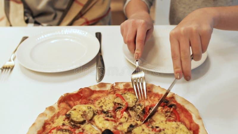 La muchacha corta una pizza para dos amigos foto de archivo libre de regalías
