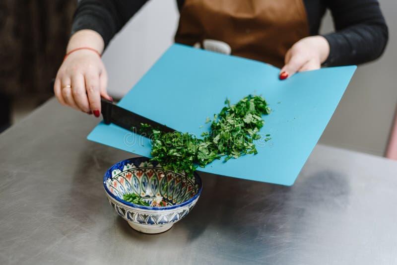 La muchacha corta verdes, cebollas, el perejil y diversos condimentos con un cuchillo en una tabla de cortar El cocinero de la mu foto de archivo