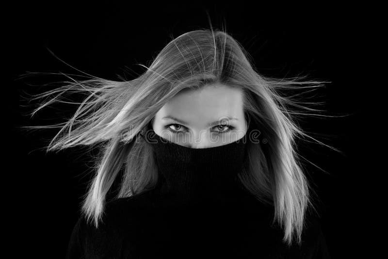 La muchacha cubre su boca con un cuello alto negro foto de archivo libre de regalías