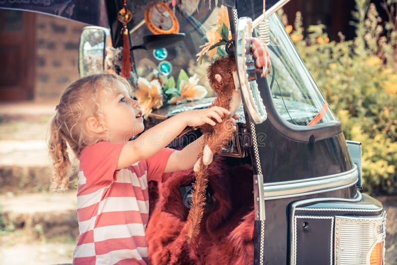 La muchacha curiosa del viajero del niño examina los juguetes en la moto del tuk del tuk durante forma de vida de la curiosidad d fotos de archivo libres de regalías